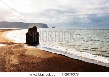 View on Kirkjufjara beach and Arnardrangur cliff. Popular tourist attraction. Dramatic scene. Location place Sudurland, cape Dyrholaey, Vic village, Myrdal Valley, South Iceland, Europe. Beauty world.