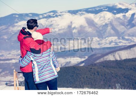 Rear view of a loving couple in fur hood jackets looking at snowed mountain range.