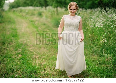 Young Overweight Girl At Beige Dress Posed Background Spring Garden.