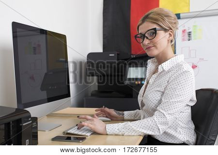 German secretary at work. Portrait of a young blonde business woman at office