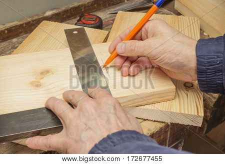 Worker Draws A Line On A Wooden Board