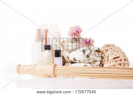Spa still life on a white background. Healthy lifestyle, body care, bathhouse, Spa treatment and relaxation concept. Bamboo massage stick, towel, moisturizing cream and other toiletry.