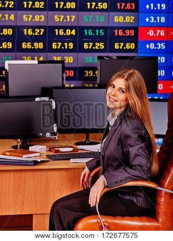 Stock exchange people. Trader woman sitting table surrounded by monitors in business office. Girl dressed in business suit.