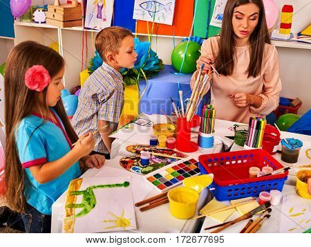 Children painting and drawing in kids club. Craft lesson in primary school. Kindergarten teacher and small students work together. Kid boy and girl coloring picture in class. Mess in classroom.