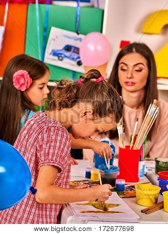 Children painting and drawing in kids club. Craft lesson in primary school. Kindergarten teacher who smiling help small students. Group people work together. Balloons decoration room.