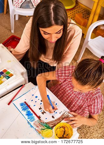 Child painting and drawing in kids club. Craft lesson primary school. Kindergarten teacher help small student. Kid girl coloring picture on table in class. Top view. Friendship with student teacher.