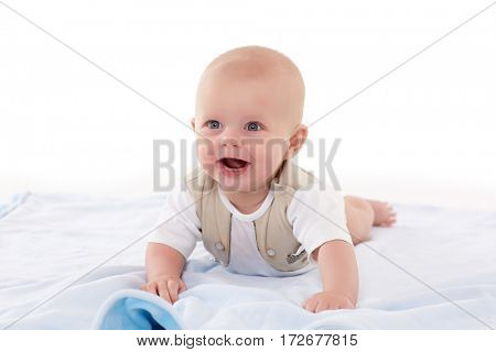Happy little baby boy is lying on his stomach  on a plaid on a white background. Six month.
