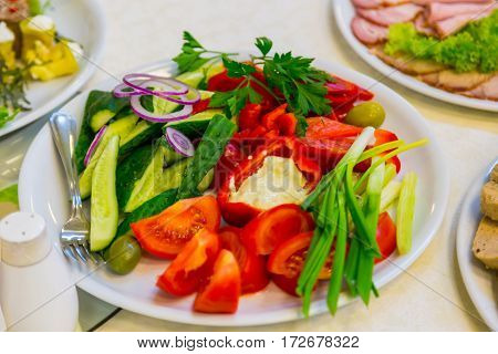 mixed vegetables on a white plate. Red peppe and tomato