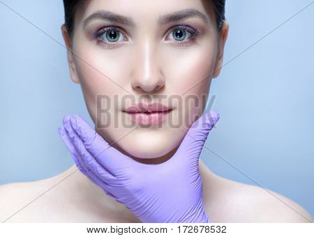 closeup portrait of attractive young caucasian woman brunette  on blue background studio shot lips face  head and shoulders skin care hands gloves lifting plastic