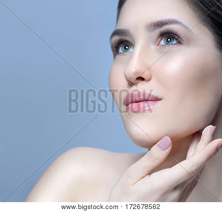 beauty closeup portrait of attractive young  caucasian woman brunette on blue background studio shot skincare face skin applying cream  looking up hands neck. fresh looking perfect skin
