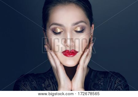 Beauty Brunette Woman with Perfect Makeup. Beautiful Professional Holiday Make-up. Red Lips perfect eyebrows. Beauty Girl's Face isolated on dark background. Eyes closed