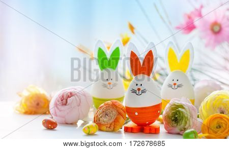 Easter decoration with funny rabbits made from eggs and spring flowers