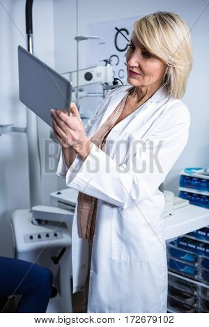 Beautiful optometrist using digital tablet in ophthalmology clinic