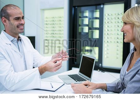 Male optometrist talking to female patient in ophthalmology clinic