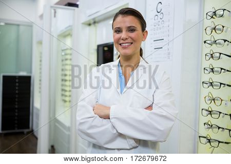 Portrait of smiling optometrist standing with arms crossed in optical store
