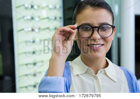 Smiling female customer trying spectacles in optical store