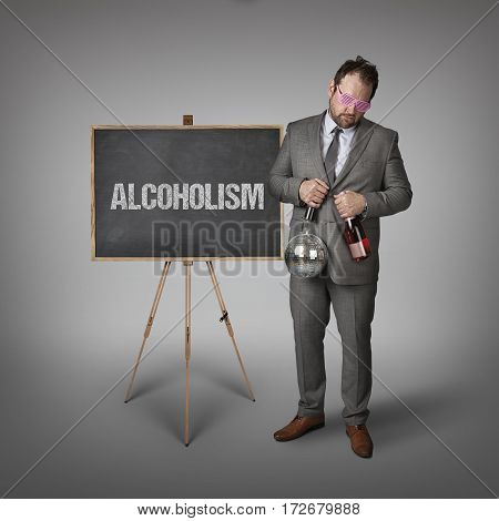Alcoholism partyman text on blackboard with businessman and key