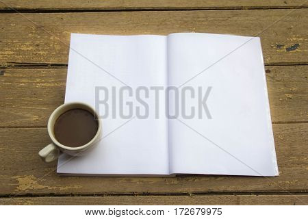 Coffee cup and note book on wooden table cup of coffee