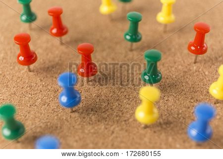 A Cork board with lot a colorful pins.
