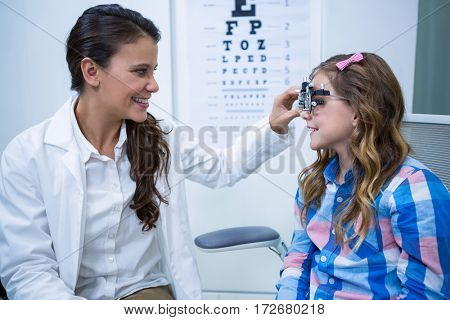 Female optometrist examining young patient with trial frame in ophthalmology clinic