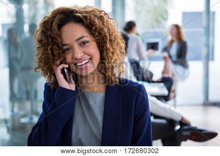 Portrait of smiling businesswoman talking on mobile phone in office