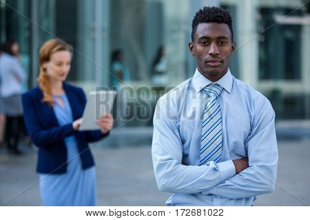 Portrait of businessman standing with arms crossed in office building