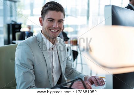 Portrait of smiling businessman working on computer in the office