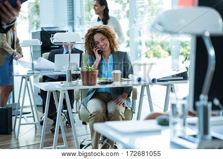 Smiling businesswoman talking on mobile phone in office