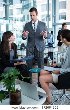 Businesspeople discussing over document at table in the office