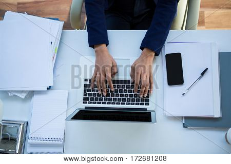Mid section of businesswoman working on laptop in office