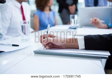 Businessman siting at table writing notes in office