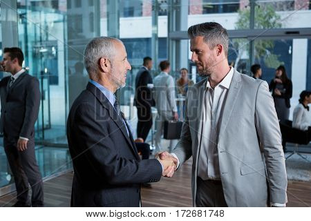 Businessmen interacting with each other while shaking hands in office