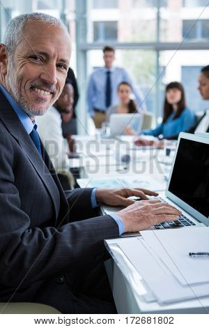 Portrait of happy businessman working on laptop in office