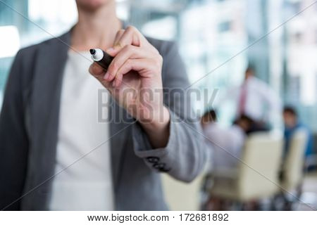 Businesswoman writing with marker on glass in office