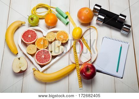 diet plan dumbbells and centimeter on a white background