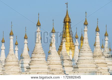 Kuthodaw Pagoda contains the worlds biggest book. There are 729 white stupas with caves with a marble slab inside - page with buddhist inscription. Mandalay, Myanmar