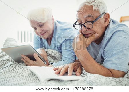 Senior couple reading a book and using digital tablet on bed at bedroom