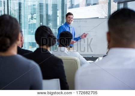 Businessman discussing on white board with coworkers in office