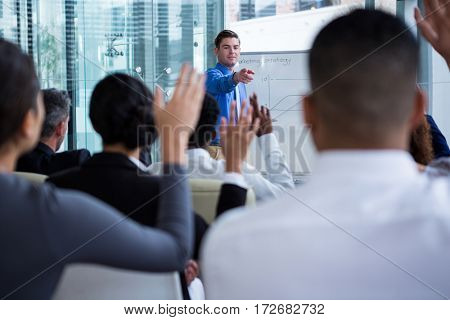 Colleagues raising their hands during meeting in office