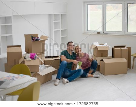 Relaxing in new house. Cheerful young couple sitting on the floor and drinking coffee while cardboard boxes laying all around them