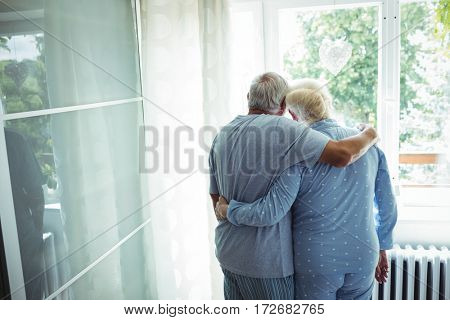 Senior couple standing with arms around at home