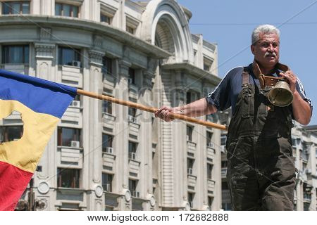 Bucharest Romania June 10 2009: A Romanian farmer with a flag protests next to the Romanian Parliament in Bucharest against the governmental measures regarding subsidies.