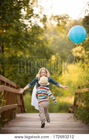 Beautiful young woman walking on wooden bridge holding big blue balloon and looking at her little cute running toddler boy on the sunset in the park. Birthday. Mother and son. Happy family..