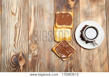 Cup With Coffee, Toast And Chocolate On Wooden Table