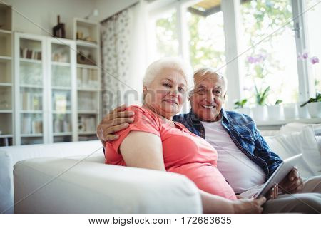 Senior couple holding digital tablet at home