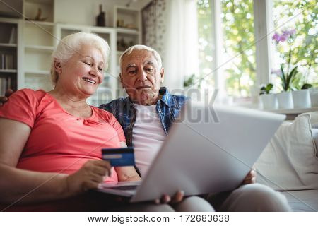 Senior couple doing online shopping on laptop at home