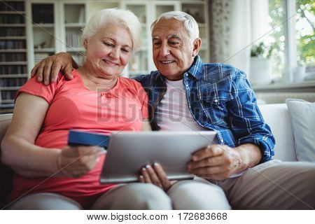 Senior couple doing online shopping on digital tablet at home