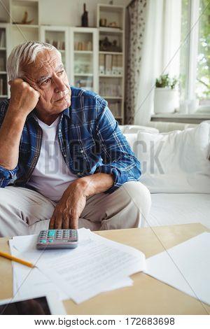 Worried senior man sitting on a sofa at home