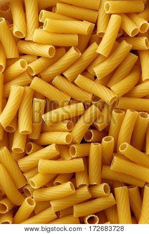 Dry uncooked rigatoni pasta background.