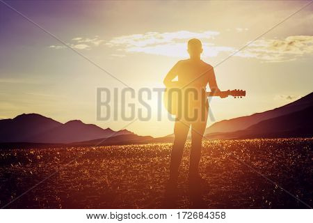 Man stands with guitar at sunset and mountains bacgdrop. Travel music concept